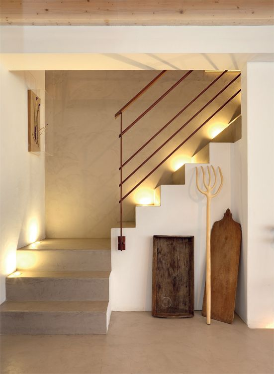 Los materiales modernos usados en la construcción mitigan la atmósfera rústica de la casa y van tejiendo un nexo cromático entre los distintos espacios. El rincón de la escalera que sube hacia el entrepiso – resaltado por una serie de spots empotrados que crean un efecto teatral– mezcla en partes iguales el cemento alisado en tonos beige con el blanco de las paredes. Enmarcadas por la silueta geométrica de la escalera, unas herramientas de trabajo antiguas dispuestas en clave escultórica…