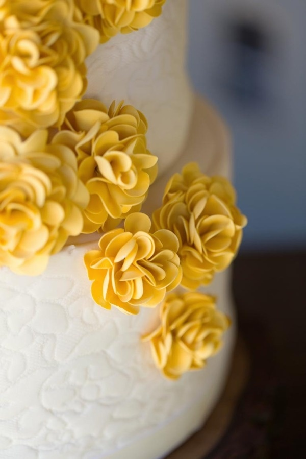 Beautiful white wedding cake with yellow flower details! Pretty!