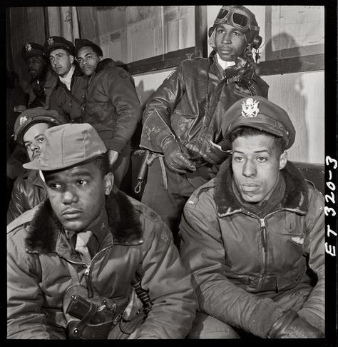 """332nd Fighter Group airmen (Tuskegee Airmen) at a briefing in Ramitelli, Italy. March 1945. Foreground: Emile G. Clifton of San Francisco and Richard S. """"Rip"""" Harder of Brooklyn."""