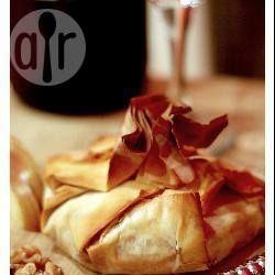 Запеченный сыр в тесте фило-Порций: 4  250 г сыра Бри или Камамбера (круглой формы) 50 г грецких орехов 2 ст.л. джема (фигового или абрикосового) 1/2 луковицы 4 листа готового слоеного теста фило 1 ст.л. меда 50 г сливочного масла, растопить