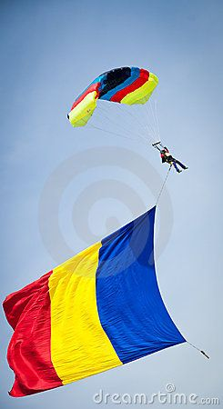 Romanian Flag Day- 26th June-© Danielnicolastudor | Dreamstime.com- Parachuter performing at an airshow carring and waving a huge romanian flag in the blue sky.