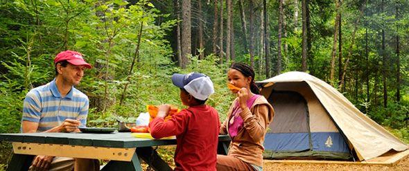 La Mauricie.   Un adulte et deux enfants prennent un repas devant leur tente en camping sauvage.