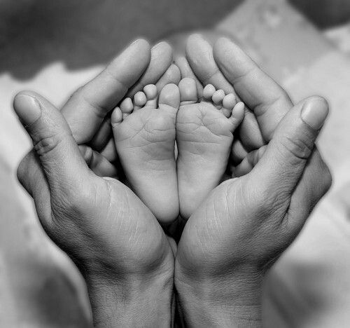 Black and white photography. Baby feet being held by the father < 3