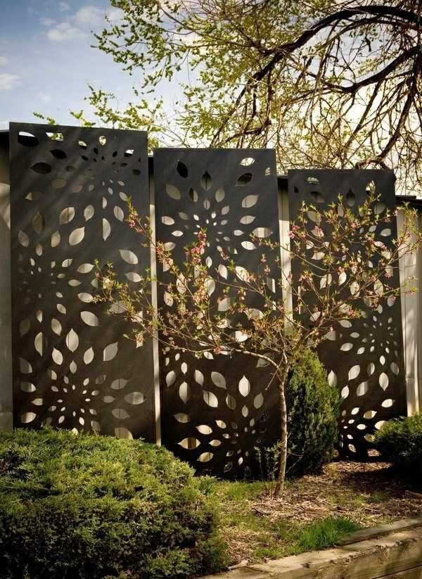Mur solide derrier les panneaux métalliques aux motifs floraux