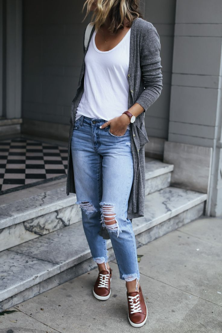 travel outfit with distressed boyfriend jeans, brown leather sneakers, and gray cardigan