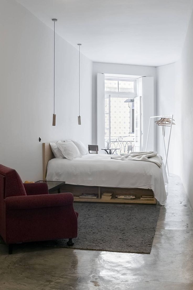 Gorgeous, minimal, industrial, scandinavian and nordic style bedroom with shiny concrete style floor, pallet bed and red armchair. By: Gustavo Guimarães