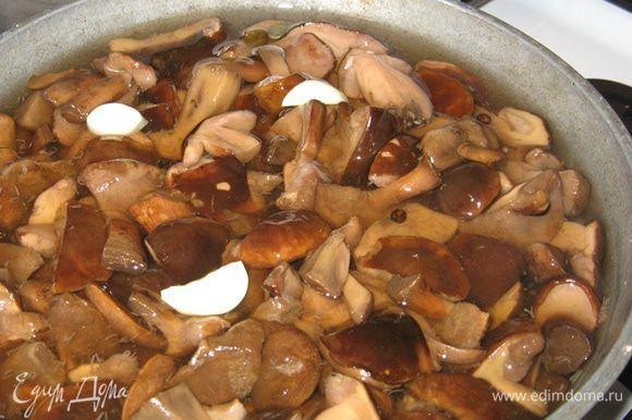 """В кипящий маринад выкладываем грибы, разрезанный на части чеснок, даем грибам закипеть, убавляем огонь и засекаем 10 минут. В самом конце вливаем уксус, перемешиваем, тут же в скоростном режиме раскладываем по банками, закатываем и вниз головой в """"баньку"""" остывать."""