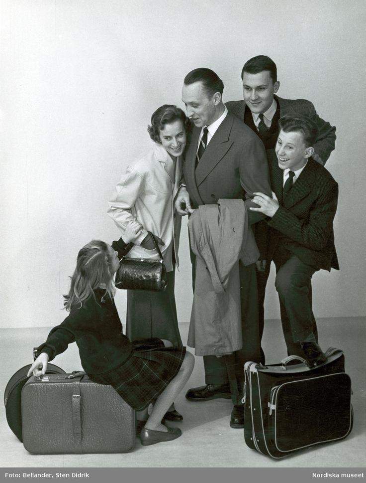 En familj med resväskor. Kvinna i jacka, kjol och väska i krokodilskinn, flicka i rutig kjol och kofta, man i kostym och rock på armen, pojkar i kavaj och slips. Fotograf: Sten Didrik Bellander, ca 1950-1959