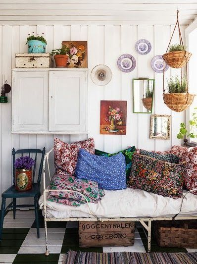 Bohemian decor incorporating floral paintings and floral cushions.