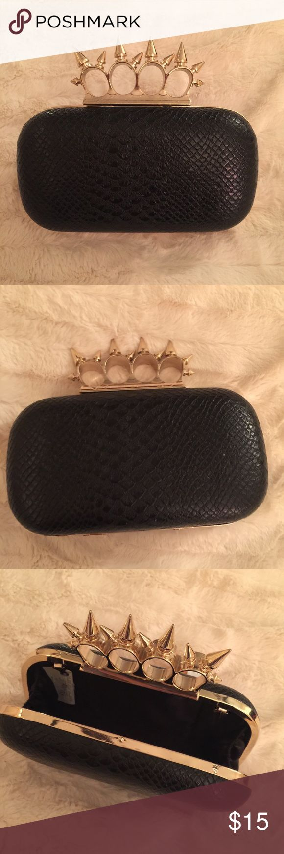 Brass knuckle clutch Never used. Tried to channel my inner Margot Robbie with her Alexander McQueen clutch, but I just couldn't rock it. Faux snake embossed with gold metal trim. Just big enough for a 7plus to fit inside. It has hooks inside for a chain, but I don't remember ever having one. Bags Clutches & Wristlets