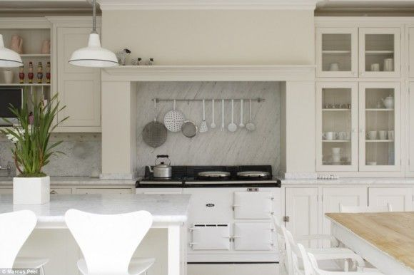 never been keen on a white kitchen - but it seems to work well here, the accent of a black top on the Aga mixing in with the grey streaking in the marble splash back.