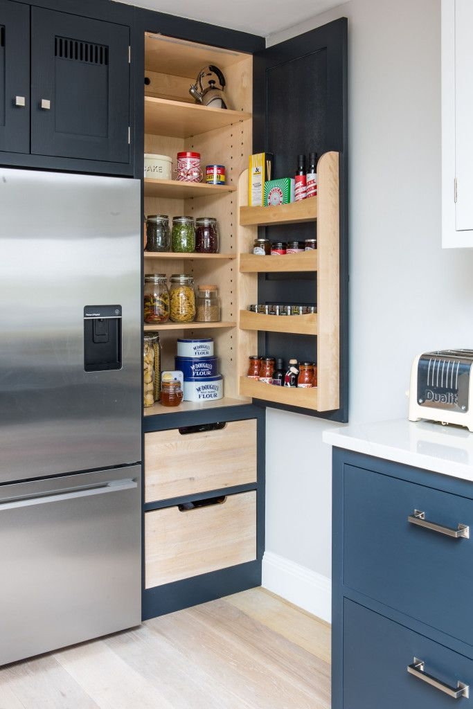 An open single larder with two pull out drawers at the bottom. The door has a birch plywood spice rack filled with spices, jars and condiments. The birch plywood adjustable shelving holds mason jars and tins. This is part of an oak shaker style kitchen painted in Farrow & Ball Railings. The larder sits to the right of  a fridge freezer.