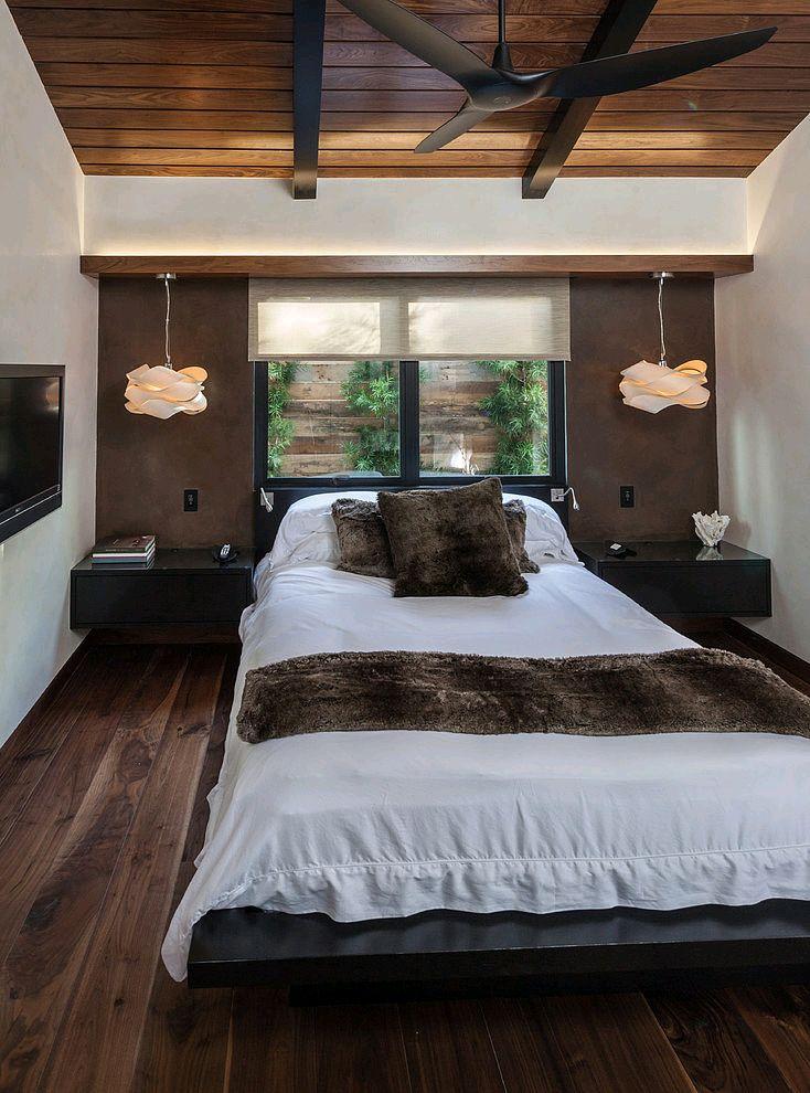 janela atrás da cama, iluminação lateral pendente e mesa de cabeceira suspensa