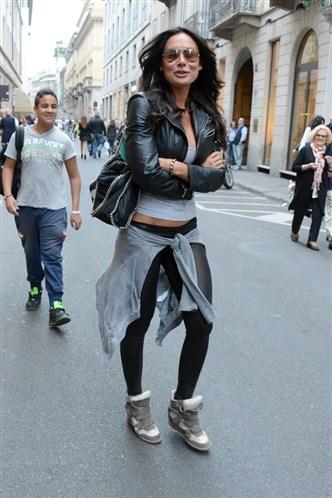 Nicole Minetti, con un look sportivo formato da leggins neri, maglietta grigia, felpa grigia annodata sui fianchi, giubbottino di pelle nera, borsa dai profili di catena e scarpe da ginnastica.