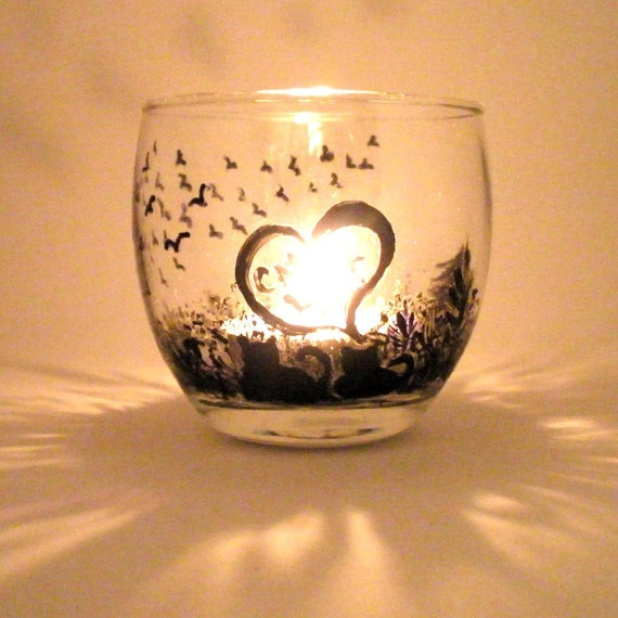 """This little hand painted votive with two cats in a love scene watching the birds. Painted in a silhouette form of black only. Is textured with a raw type of painting. Heart with words """"Cat Love"""" completes this real cute scene."""