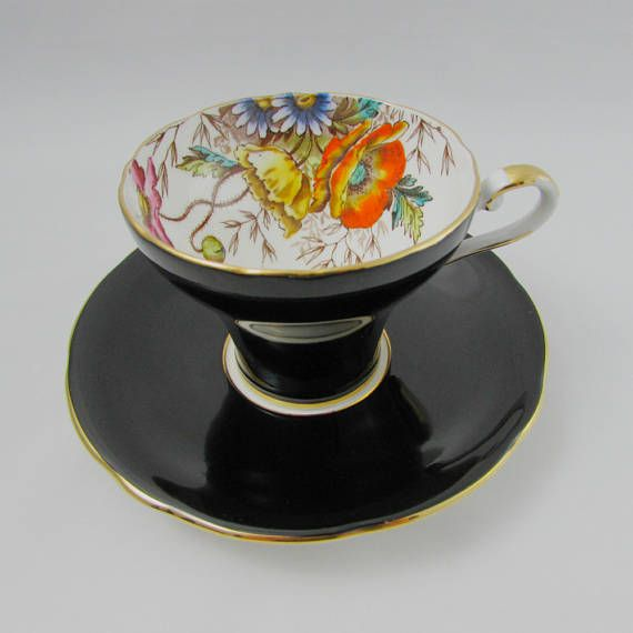 Gorgeous tea cup and saucer set made by Aynsley with large hand painted poppy flowers. Gold trimming on cup and saucer edges. Excellent condition (see photos). Markings read: Aynsley England Bone China Please bear in mind that these are vintage items and there may be small