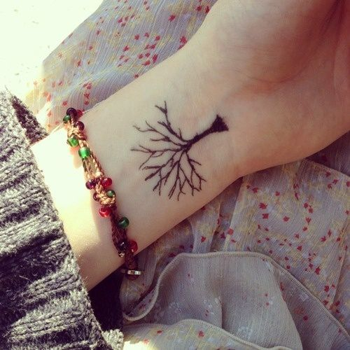 Pequeño tatuaje de un árbol sin hojas en la muñeca.