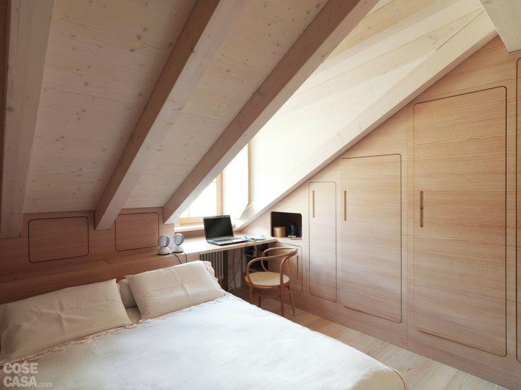 dietro il letto, la struttura in legno realizzata su misura somma più funzioni: distanzia la rete dalla parete esterna e dalla parte più bassa dello spiovente, permettendo inoltre di ricavare capienti vani nello spessore
