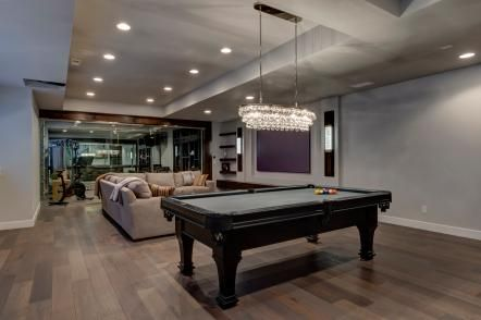 Once a dark and confining basement, this downstairs space has been transformed by the Finished Basement Company into a bright family room that bursts with activity. A stocked wine cellar, pool table, gym and lounge give the residents many ways to entertain guests.