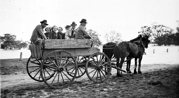 A group of people in a horse-drawn cart, with floodwaters in the back-ground, the road disappears under water on the right, Horsham district, c1935.