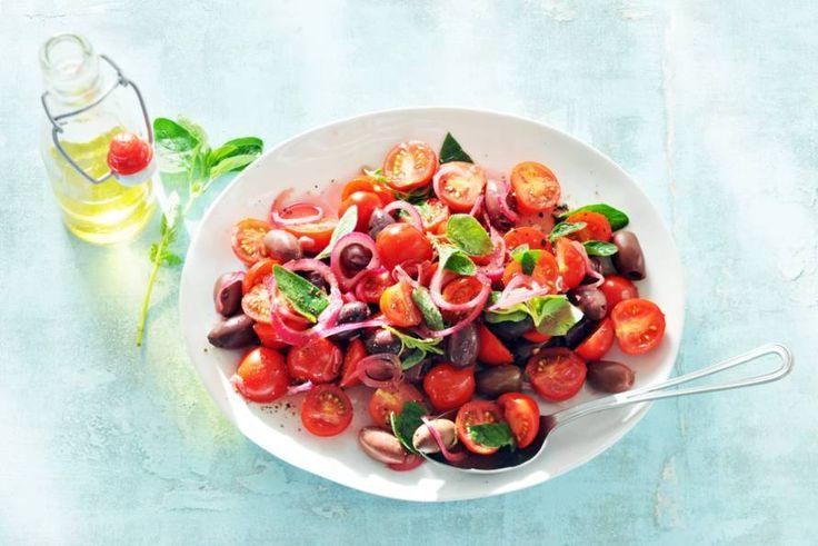 Basilicum, oregano, olijven en stevige, volzoete romaatjes: mediterraner krijg je het niet in deze tomatensalade - Recept -Allerhande