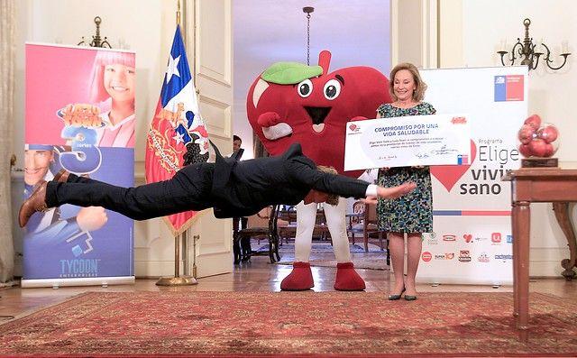 """05 de Diciembre de 2012/SANTIAGO_.  El actor Magnus Scheving (Sportacus), realiza una serie de pieruetas mientras la primera dama Cecilia Morel sostiene el convenio de colaboración firmado entre el programa """"Elige Vivir Sano"""" y """"LazyTown"""", para promover la vida sana en los preescolares chilenos, en el Palacio de La Moneda_.  FOTO: PEDRO CERDA/AGENCIAUNO_."""