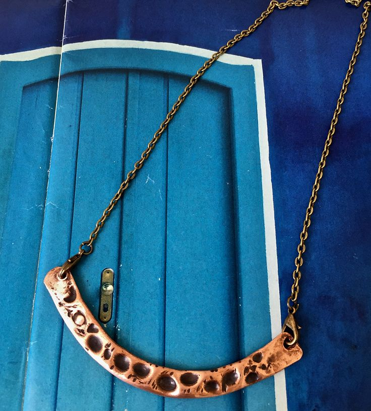 The pendant on this arch necklace is formed by hand from solid rosy copper.