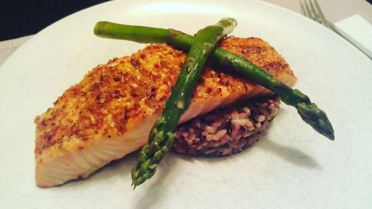 Maple glazed herb encrusted salmon on top of wild rice topped with steamed asparagus.