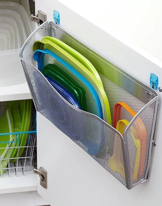 Attaching a file organizer to the inside of your cupboard would give you a place to store your lids so you always know where they are.