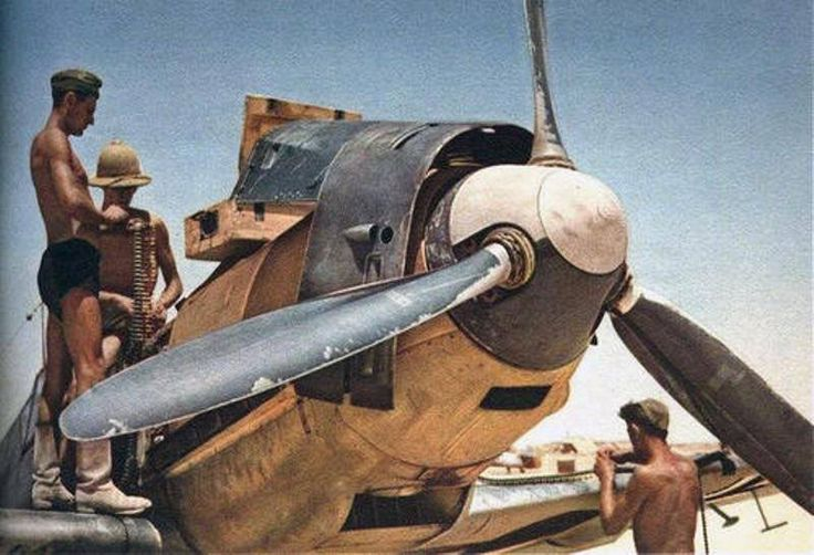 German armorers reloading the weapons of a X Flieger Korps, Flieger Führer Afrika,'s Messerschmitt Bf 109E on a Libyan airstrip, likely 1941. The photo give an idea of the sand's effects over the airplane's forward section. The dark paint of the propeller's blades is scraped by the continuous high speed projection against the propeller of the microscopic sand's grains, in addition to natural erosion of the metal propellers.