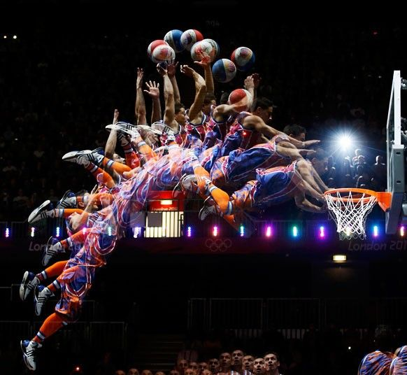 A member of the 'Crazy Dunkers' group performs a dunk during an interval of the men's preliminary round Group B basketball match between Australia and Russia at the Basketball Arena