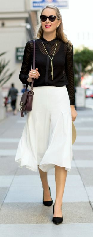 ivory pleated culottes, sheer black chevron button front collared shirt, lariat necklace, block heel suede pumps, straw wide flat brim hat, burgundy cross-body bag with chain and tassel detail