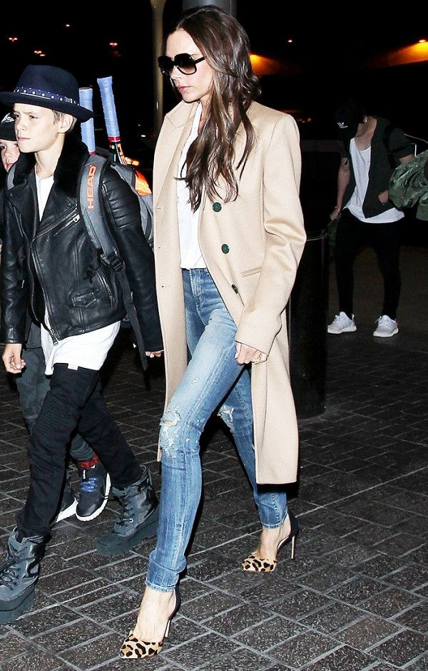 Victoria Beckham wearing skinny jeans and a camel trench coat.