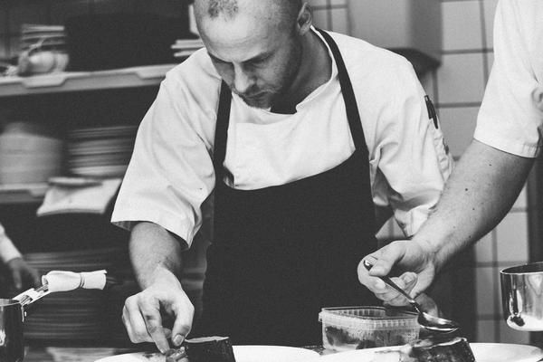 Jack Dusty Clothing - Uniforms - Black and White picture of a Chef, wearing a black apron and white uniform uniform plating up.