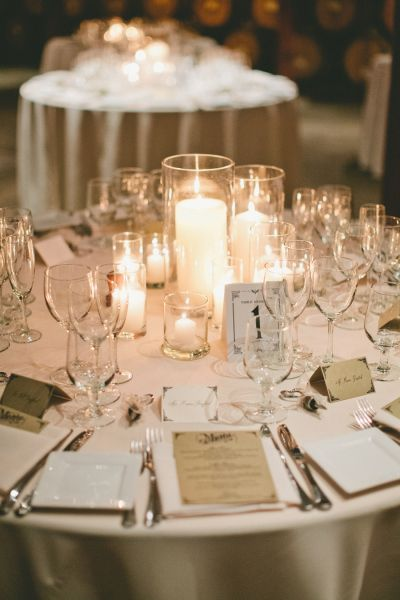 Use candles and clear glass instead of flowers. I like this for fall or winter weddings. - onelove photography