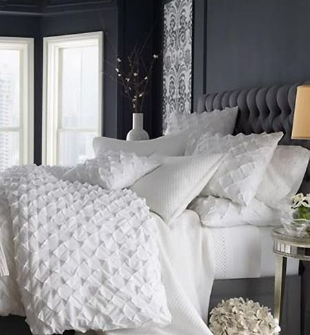 I love the textured bedding here. The dark walls are countered well with the white bedding and the textures of the headboard and bed spread look really nice.