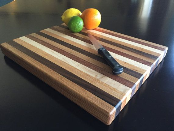 The pictured cutting board has been sold, and a new one will be available shortly. This rectangle shaped cutting board is hand crafted from various hardwoods including hickory, maple, cherry, walnut, and mahogany. These contemporary cutting boards are designed and meticulously handmade by cutting, gluing and clamping strips of various hardwoods. They are then cut to shape, sanded and finished with many coats of Howard butcher block and cutting board oil to establish and maintain a natural…