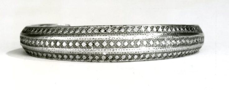 Silver arm-ring with faceted outer faces; stamped geometric decoration; narrowing to zoomorphic terminals. Graham-Campbell 1980. No find-details for this example of the commonest type of Gotlandic silver arm-ring, Stenberger's Type Ab.2 (Stenberger, M. (1958): 'Traditionsbundenhet i vikingatida gotländsk brakteatkonst', Tor, iv, 107-9, fig. 13), as nos. 7-8 in the Martens hoard (Stockholm (Statens Historiska Museum): SHM 12151:7-8). Middle /Late Viking Period. British Museum: 1921,1101.305.