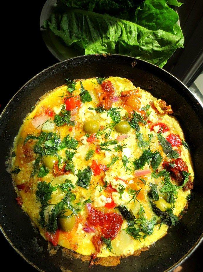 Omelette à la Grecque 8 œufs bio 80g d'olives noires ou vertes 1 grosse tomate 1 oignon rouge 1 poivron frais (que j'ai utilisé grillés à l'huile que j'avais en stock) 130g de feta 1 petite pomme de terre sans peau cuite à l'eau Aneth, persil, coriandre, menthe frais Huile d'olive Sel et poivre