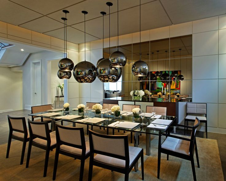 Bronzed mirror panels set in the dining room's painted panel walls reflect the furnishings and art. The highly-reflective, playful pendant lights create infinite layers of color and shape, adding complexity to the very simply finished room.