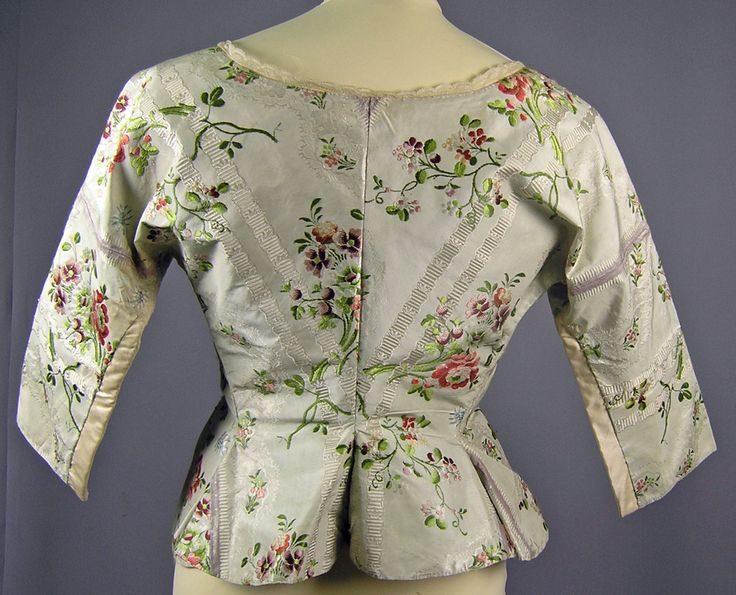 Rear view, bodice, c. 1770-1780. Pale green silk brocade embroidered with floral and leaf patterns, lace trimming.