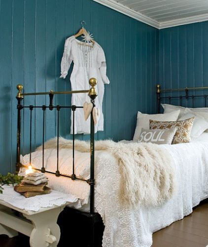 teal wall, white bed coverings, black and gold bed frame