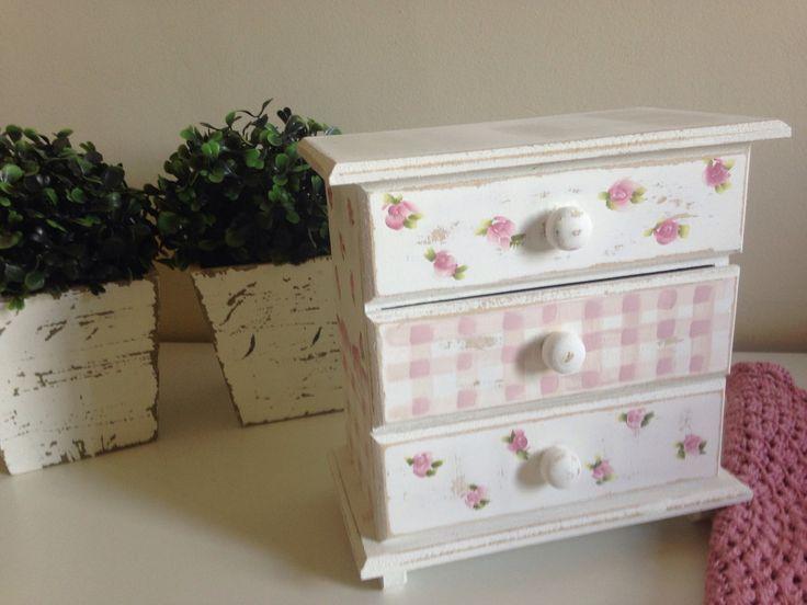 Mini cômoda pintada a mão, trabalhada com técnica provençal decorada com laço, pintura xadrez e mini rosas. <br>Peça composta de 03 gavetas. <br>Dimensões do produto: 15x15x15cm (LxCxA)