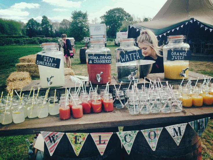 Welcome drinks table with cocktails, jam jars, mason jar drinks dispensers and bunting. Wedding cocktails / Drinks Station