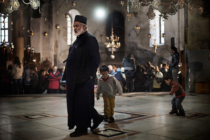 Bethlehem, West Bank: A Christian Orthodox priest walks past children playing inside the Church of the NativityPhotograph: Marco Longari/AFP/Getty Images