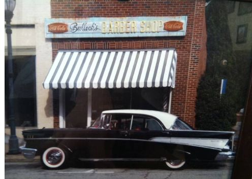 Old classic car in front if an old downtown barber shop.
