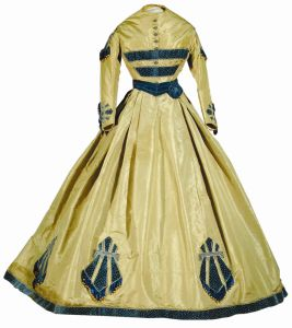 Smoke-Blue Silk, 1865  This gown was worn to President Abraham Lincoln's inaugural ball held after his re-election. Margaret Usher attended the ball with her husband John, who was Secretary of the Interior. The Ushers eventually settled in Lawrence, Kansas.    Three pieces make up this gown--a bodice, skirt and short jacket. All are of greenish-gray silk taffeta, and trimmed with blue velvet, plush fringe, and gold-colored silk balls. The jacket is trimmed with velvet epaulettes, in keeping…