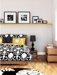 Shelf idea. I like the room. cool colours and a nice atmosphere. I quite like that idea of having photo frames on a shelf, above the bed, with a black and white rug. I also like the lamp.