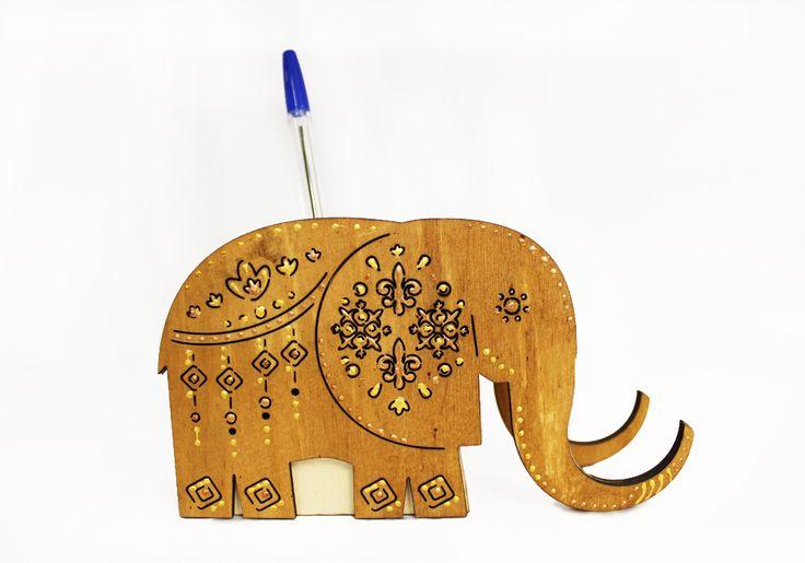 Карандашница в виде слона с подставкой для сотового телефона вырезана из березовой фанеры с использованием лазерной технологии. Окрашена морилкой в коричневый цвет, и расписана золотым акриловым контуром. Размер карандашницы в высоту 9,5 см, в длину 16,5 см, в ширину 5 см. Карандашница подойдет для продажи в магазинах с сувенирами и канцелярией. Ее можно подарить другу на день рождение или любой другой праздник.