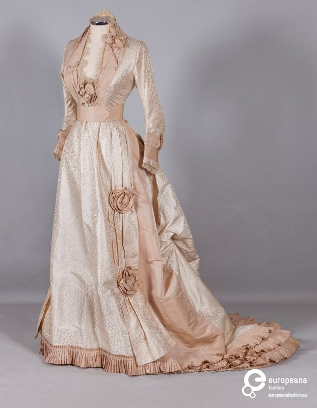 Wedding dress in ivory brocade with woven paisley motifs, trimmed with beige organza bows and pleated beige taffeta frills, United States, 1870.